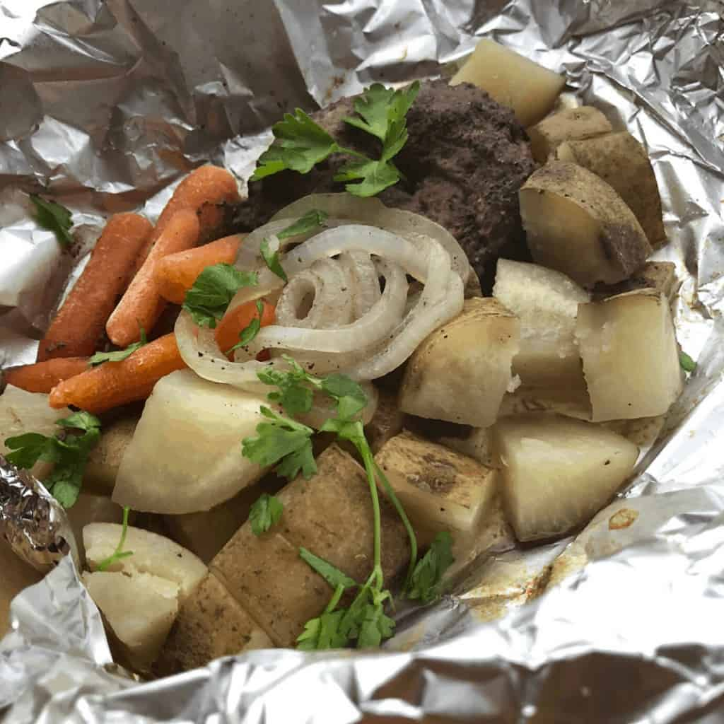 A hobo dinner consisting of hamburger, carrots, and potatoes on aluminum foil
