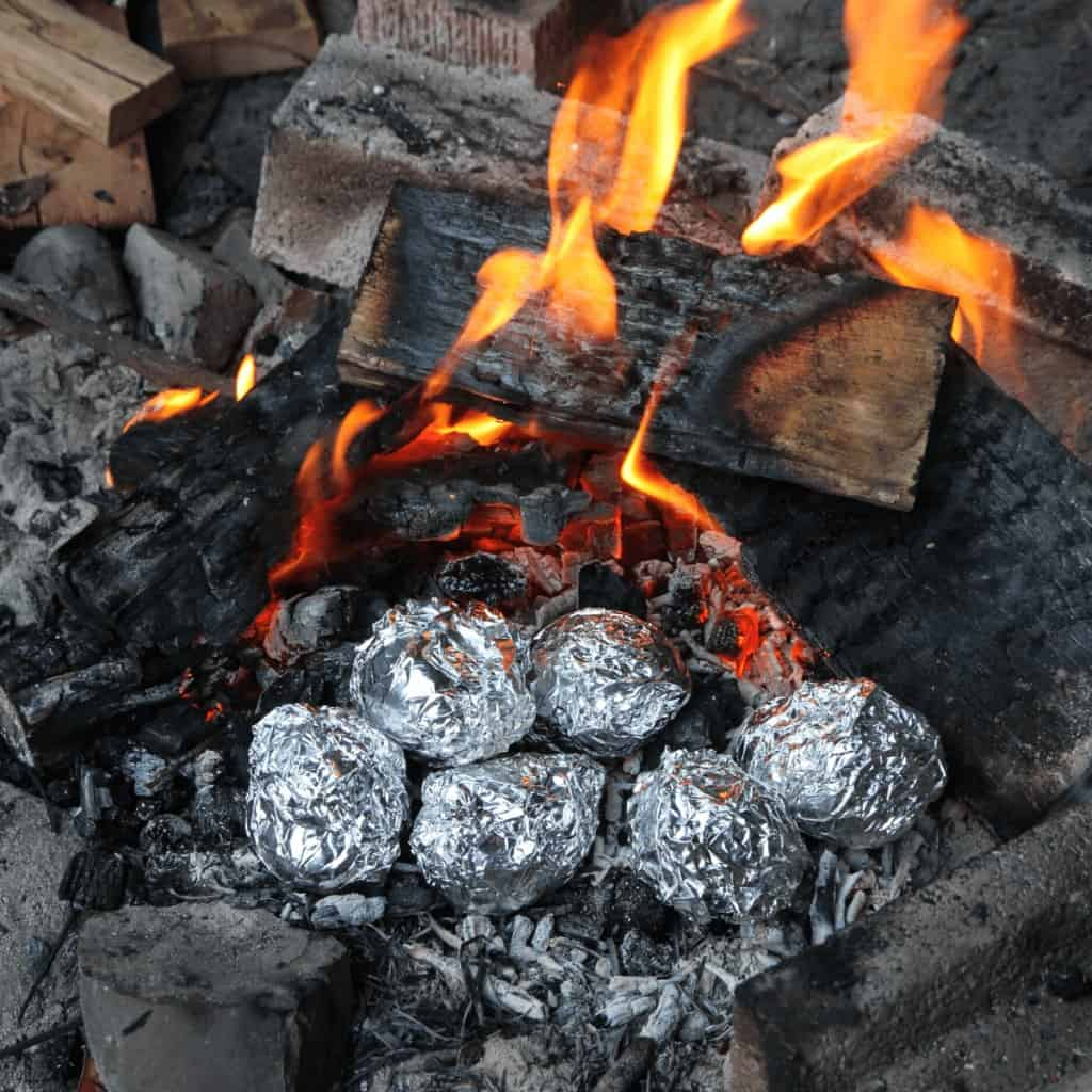 A campfire with food wrapped in foil cooking