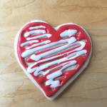 A heart sugar cookie with white and red icing