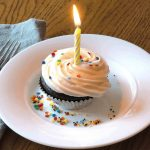 A birthday cupcake topped with vanilla dairy free frosting