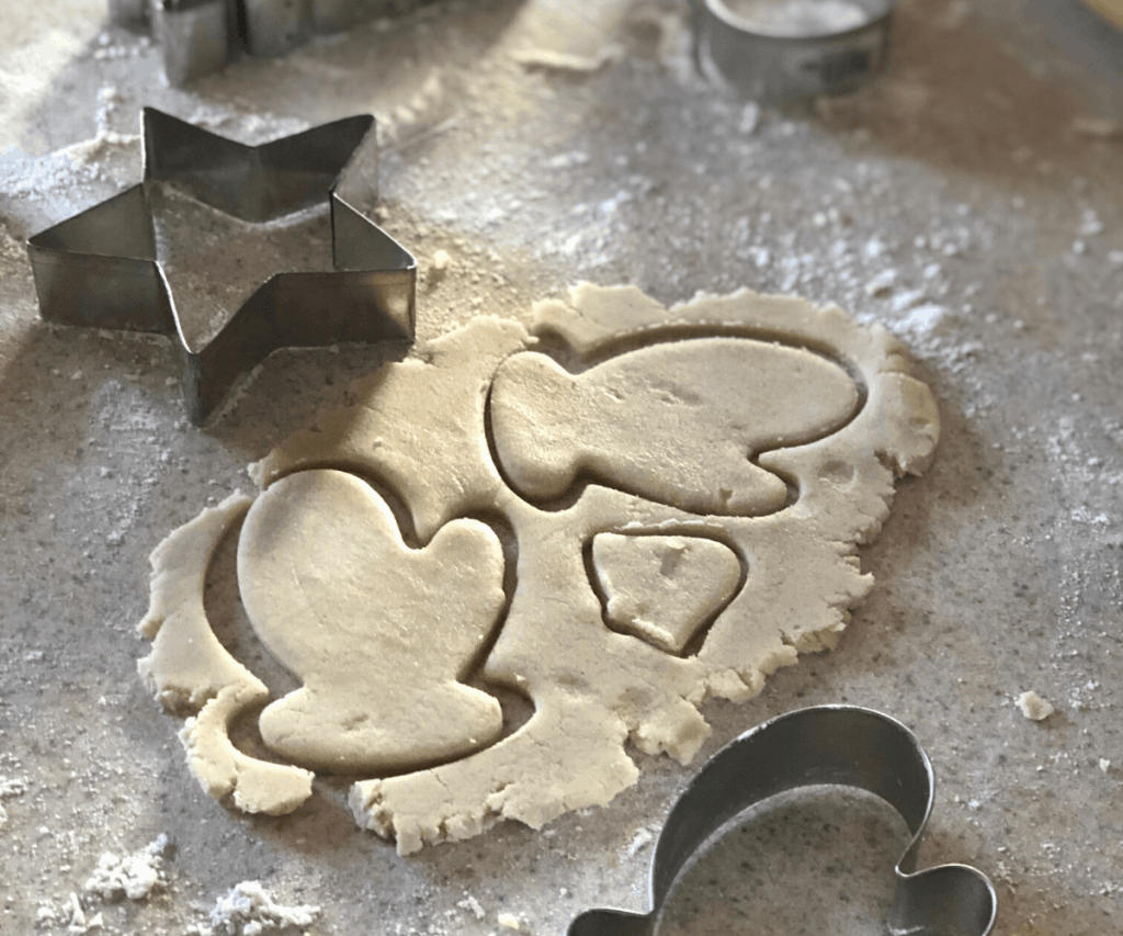 Two mitten-shaped gluten free cookie cutouts