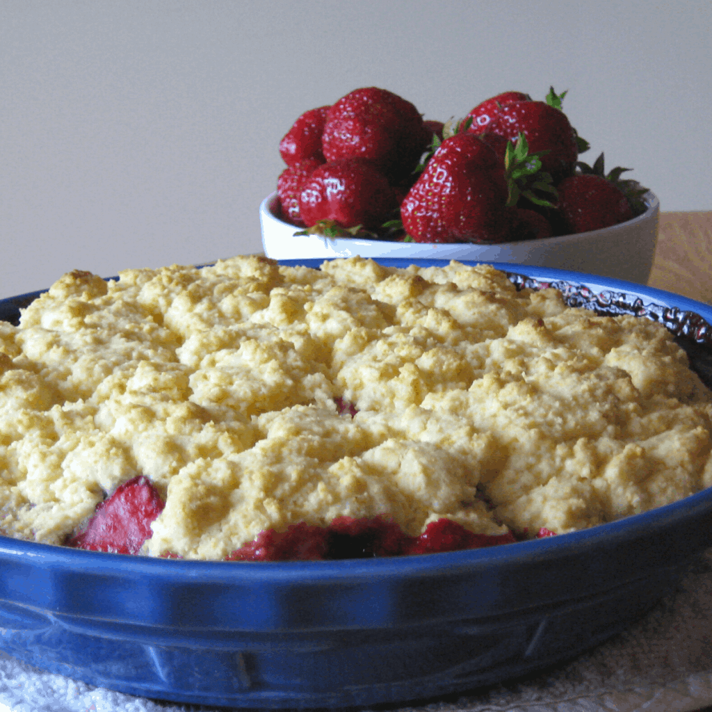 Strawberry rhubarb cobbler in front of a bowl of strawberries