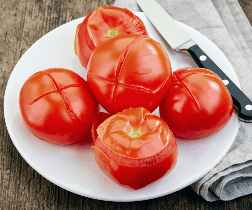 A plate with blanched tomatoes and a knife