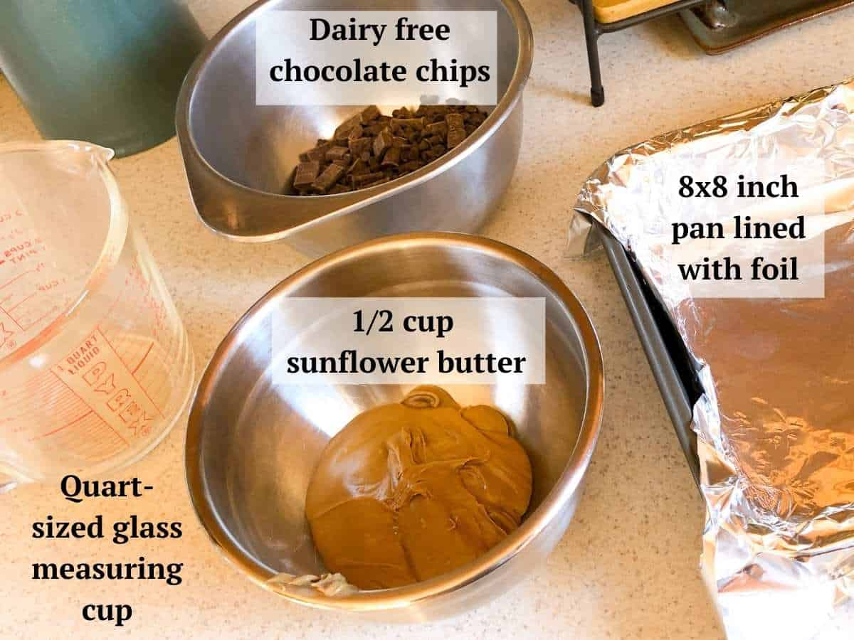 Some ingredients needed to make the dairy free fudge including dairy free chocolate chips, sunflower butter, an 8 inch square baking dish lined with foil , and a quart sized measuring cup.