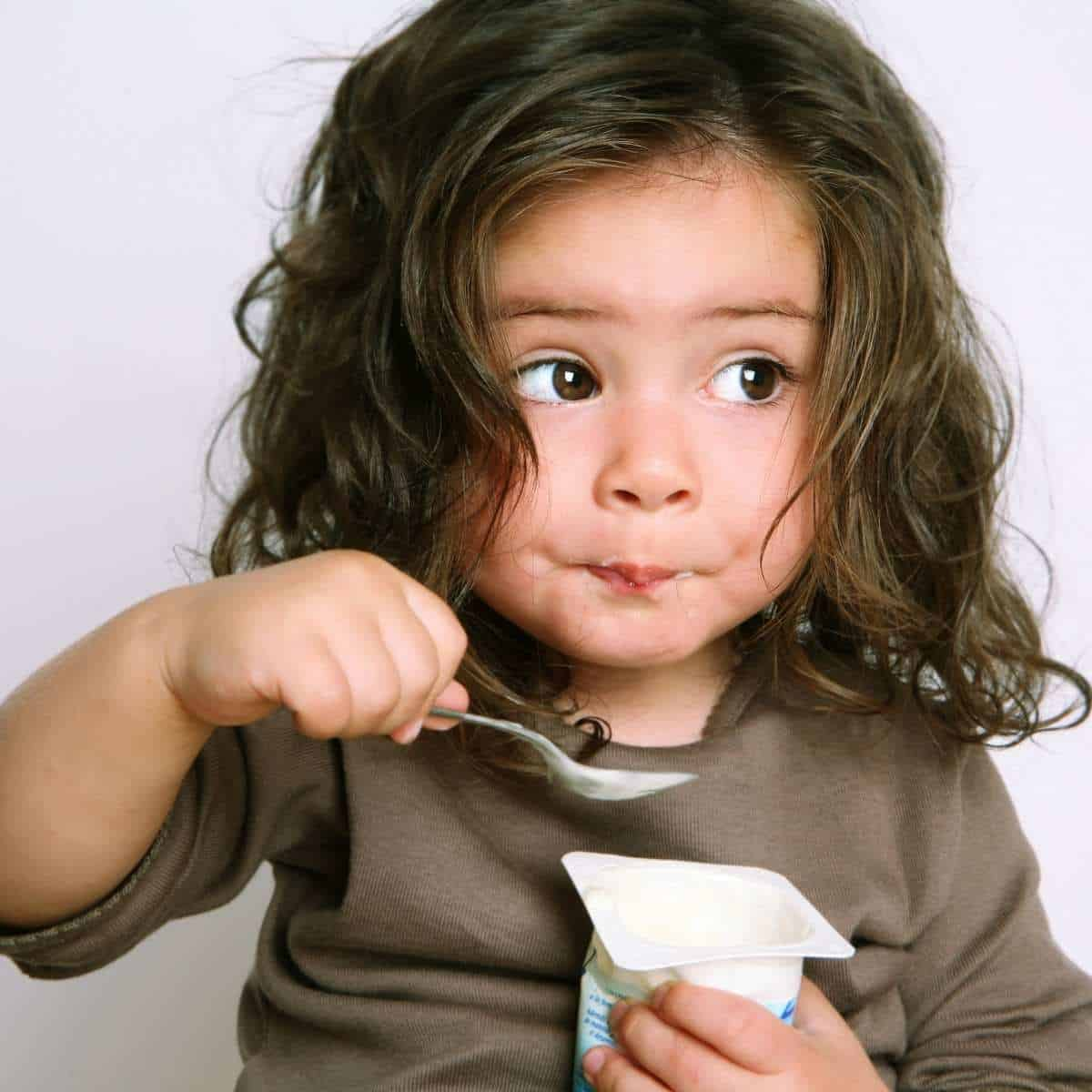 Child eating dairy yogurt with allergy free protein power added