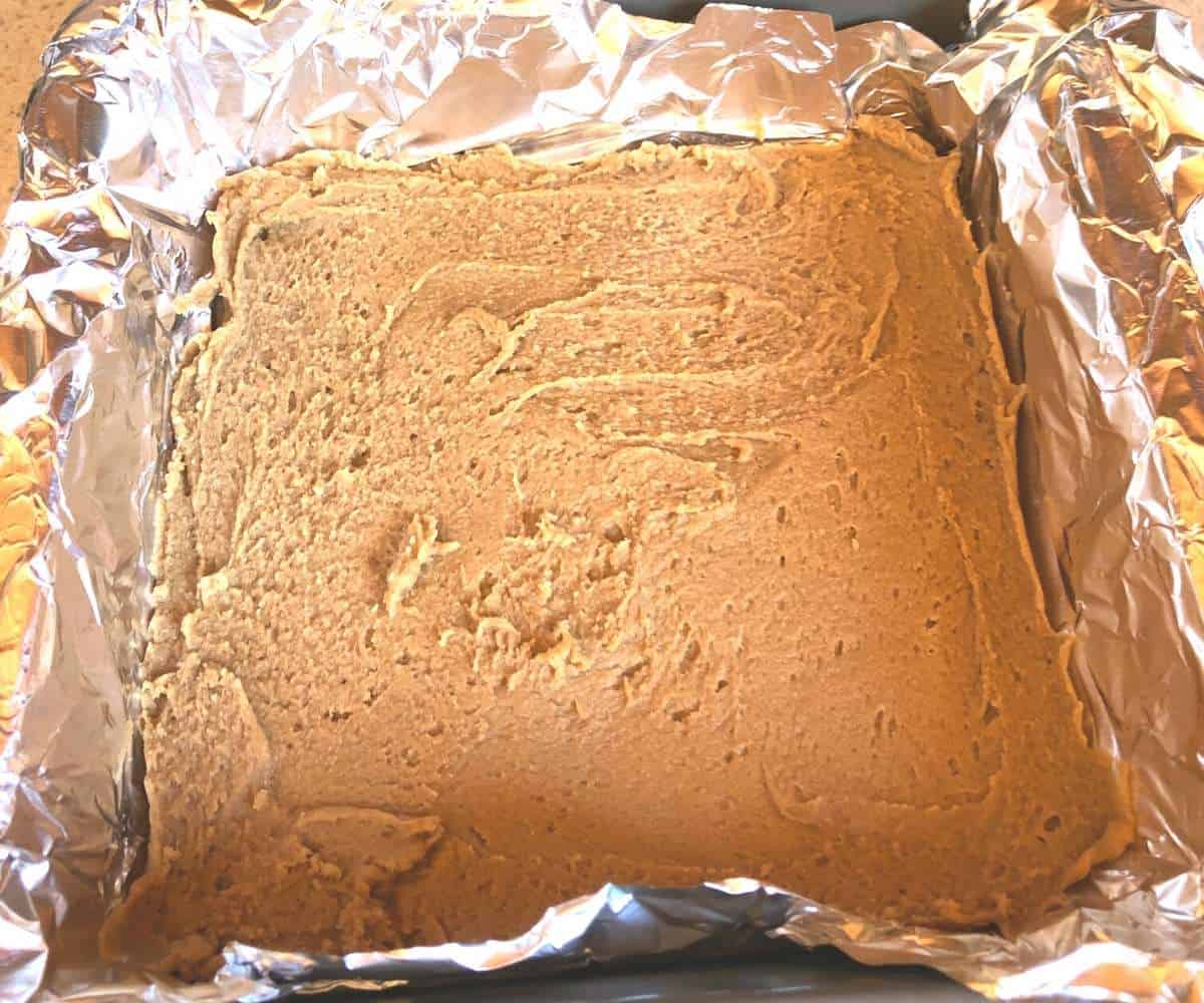 A layer of sunflower butter fudge spread in a pan.