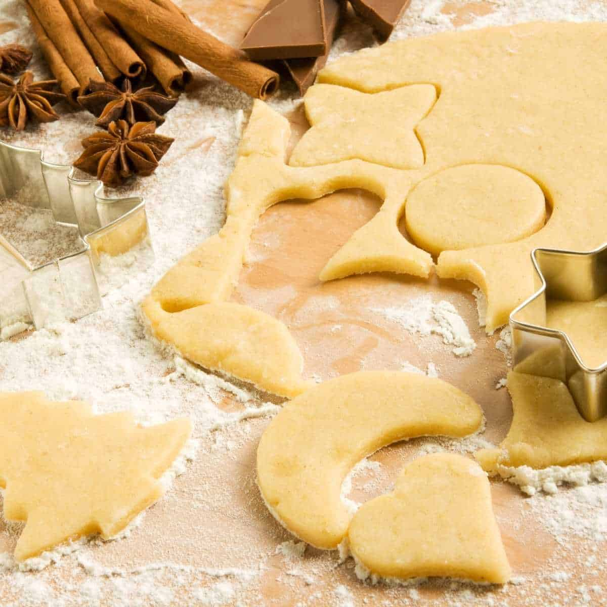 Allergy friendly Christmas cookies being cut out on a floured board