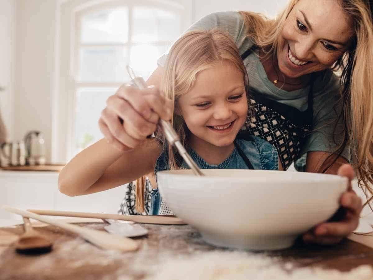 A woman and girl stirring batter in a bowl.