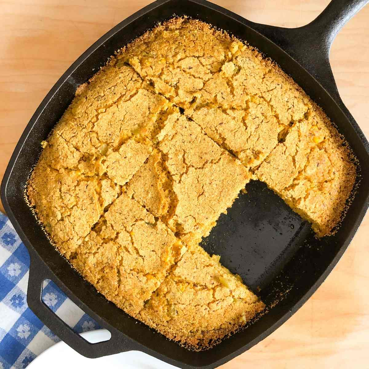 A skillet with gluten free cornbread cut into squares.