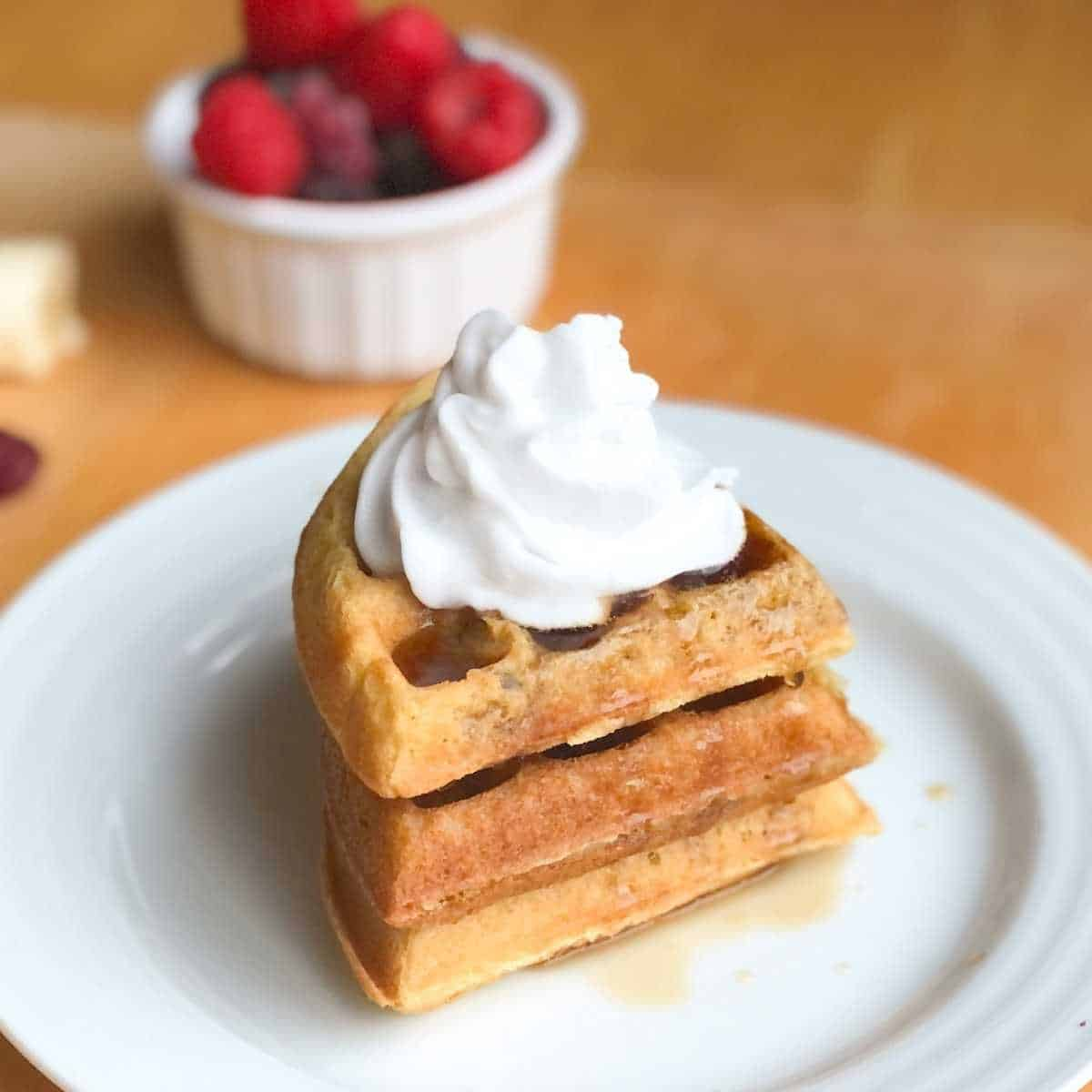 Two dairy free waffles topped with coconut whipped cream and maple syrup.