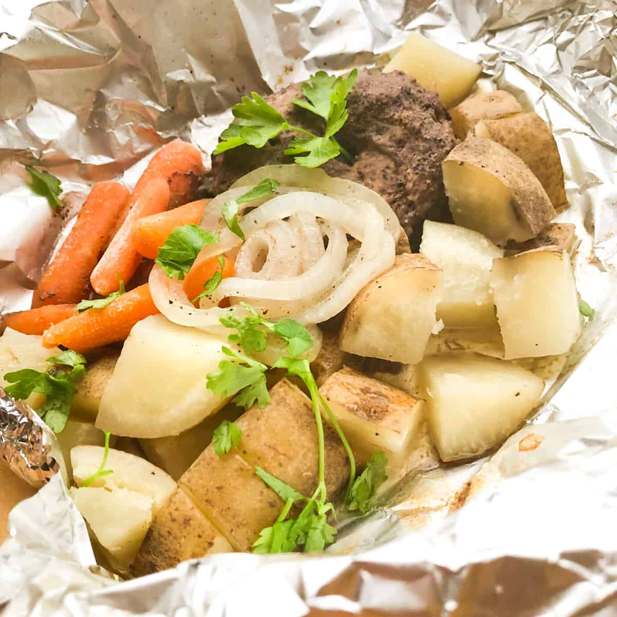 A hamburger foil packet with potatoes, carrots, and onions