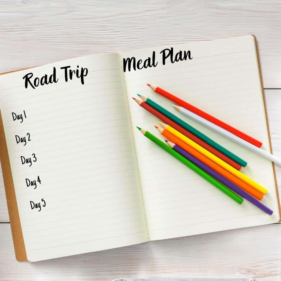 A lined journal with a road trip meal plan and colored pencils on it.